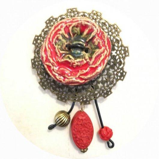 Broche coquelicot bouton en céramique rouge sur fond filigrané bronze avec breloques bronze et perles rouges