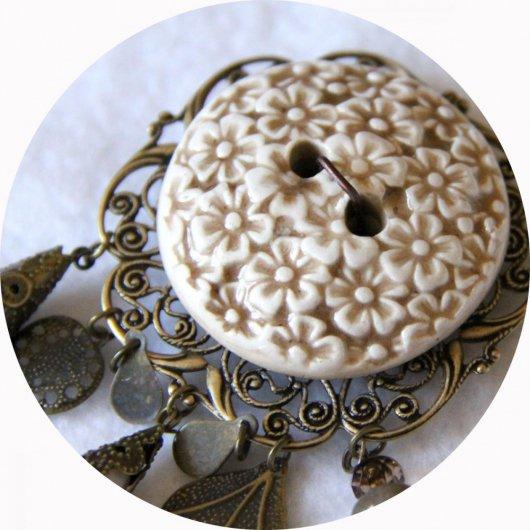 Broche ronde bouton en céramique beige et ivoire sur fond filigrané bronze avec breloques bronze et perles crème