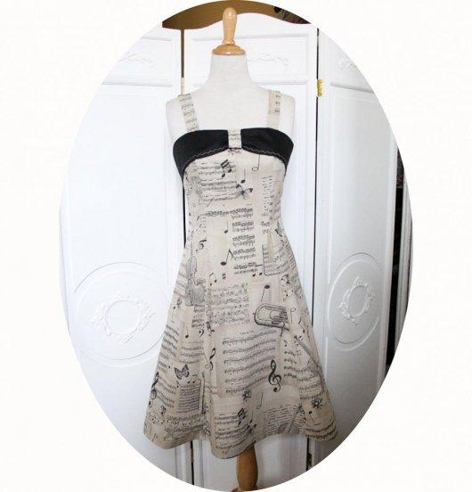 Robe thème musique en coton beige imprimé instruments et notes de musique noires ajustée sur le buste avec une jupe évasée et bandeau noir